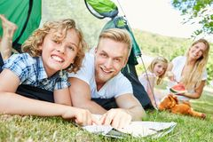 Father and son with map at camping. Father and son camping in tent with map plan together a trip royalty free stock image