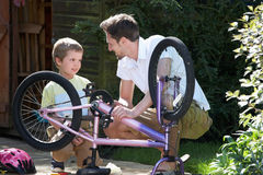 Father And Son Mending Bike Together Royalty Free Stock Photography