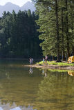 Father and son (8-10), in mid-distance, fishing in lake on camping trip, mother and daughter (7-9)approaching Stock Image