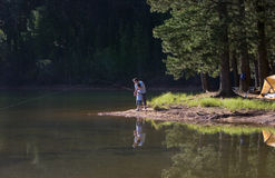 Father and son (8-10), in mid-distance, fishing in lake on camping trip, side view Stock Photos