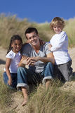 Father, Son & Mixed Race Daughter Sitting on Beach. A man mixed race girl and young boy, father, son and daughter, sitting down and having fun in the sand dunes Royalty Free Stock Image
