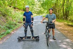 Father and son with mountain bike and mountainboard. Father and son standing with mountain bike and mountainboard on road royalty free stock image