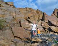 Father and son on a mountain ledge. Father and his young son on a mountain ledge standing celebrating the sunshine and open air with their arms outstretched and Royalty Free Stock Image