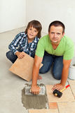 Father and son mounting ceramic floor tiles together Stock Images