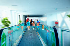 Father and son moving on escalator after arrival in international airport Stock Photography