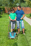Father and son mowing the lawn Stock Photography