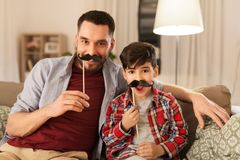 Father and son with mustaches having fun. Family, childhood and fatherhood concept - happy father and little son with mustaches party props having fun at home royalty free stock images