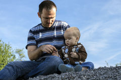 Father and son sitting together in nature stock images