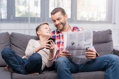 Father and son with newspaper and smartphone. Smiling father with newspaper and cute little son using smartphone together at home Royalty Free Stock Photos