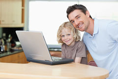 Father and son with notebook in the kitchen Stock Photography
