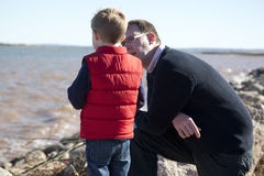 Father and son by the ocean. Father and son standing on the shore beside the ocean deep in conversation royalty free stock images
