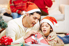 Father and son opening gifts at Royalty Free Stock Image