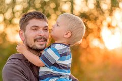 Father and son outdoor portrait in sunset sunlight Royalty Free Stock Photography