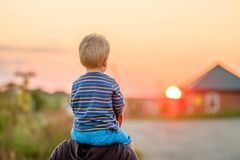 Father and son outdoor portrait in sunset sunlight stock photo