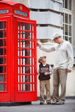 Father and son outdoors by red phone booth Royalty Free Stock Images