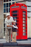 Father and son outdoors by red phone booth Stock Images