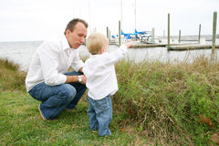 Father and son outside. Young boy and father spending time together at a marina Royalty Free Stock Photos