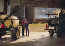 Father with son outside barn. Farmer with son at barn overlooking property Royalty Free Stock Photo