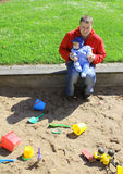 Father and son outside playing in sandpit Royalty Free Stock Photo