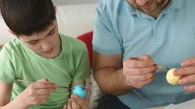 Father and son paint eggs together on Easter stock video
