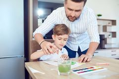 Father and son paint on the paper at the table. Father and son paint on the paper at the table in the room. Father`s Day Royalty Free Stock Photos