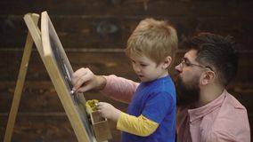 Father and son painted with chalk on a board. Side view of little boy and father with pieces of chalk drawing picture on stock video footage