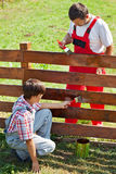 Father and son painting a garden fence Royalty Free Stock Images