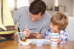 Father and son painting model ship. And smiling off camera royalty free stock photo