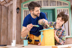 Father and son painting small wooden birdhouse on porch Stock Image