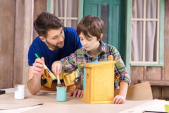 Father and son painting wooden birdhouse together Royalty Free Stock Photography