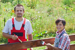 Father and son painting a wooden fence Royalty Free Stock Photo