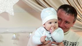 Father and son, a parent and baby play in the home in the winter, a happy family, a good dad keeps a small child in his stock video footage
