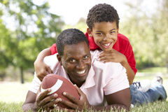 Father And Son In Park With American Football Royalty Free Stock Photos