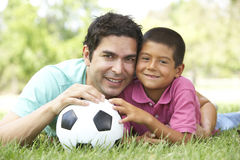 Father And Son In Park With Football. Father And Son In Park With Soccer Ball Smiling To Camera Royalty Free Stock Photo