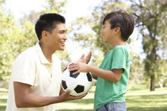 Father And Son In Park With Football. Asian Father And Son In Park With Soccer Ball Smiling Royalty Free Stock Photos