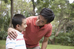 Father And Son In Park. Happy father and son arm around in park Stock Photos