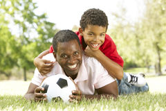 Father And Son In Park With Soccer Ball. Smiling To Camera Royalty Free Stock Photos