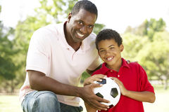 Father And Son In Park With Soccer Ball. Smiling Stock Photography