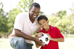 Father And Son In Park With Soccer Ball. Smiling Stock Photo