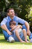 Father and son at park. Young boy resting against father in a park holding soccer ball. Smiling father and son with a football in the park on a sunny day. Happy Royalty Free Stock Photo