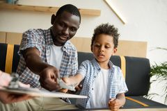 Father and son paying bill Stock Photography