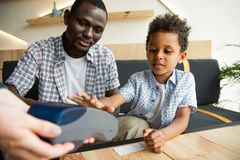 Father and son paying bill Royalty Free Stock Images