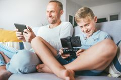 Father and son, PC gamers, enthusiastically playing with electronic devices: tablet and gamepad stock photo