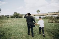 Father son go meadow lake together black. Father and son, the peasants go along the meadow to the lake together in black clothes and white shirts stock images