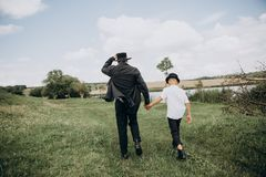 Father son go meadow lake together black. Father and son, the peasants go along the meadow to the lake together in black clothes and white shirts royalty free stock photo