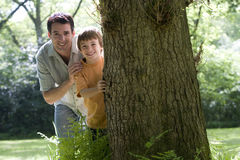 Father and son (8-10) peeking out from behind tree, smiling, portrait royalty free stock photos