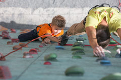 Father and son perform speed climbing relay race Stock Image