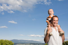 Father son piggy back. Father carrying his son on piggy back ride outdoors against nature and blue sky Royalty Free Stock Photography
