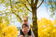 Father and son piggyback in autumn park. Father giving his son piggyback ride in autumn park, Adelaide Hills, South Australia stock images