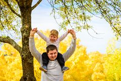 Father and son piggyback in autumn park. Father giving his son piggyback ride in autumn park, Adelaide Hills, South Australia royalty free stock photos
